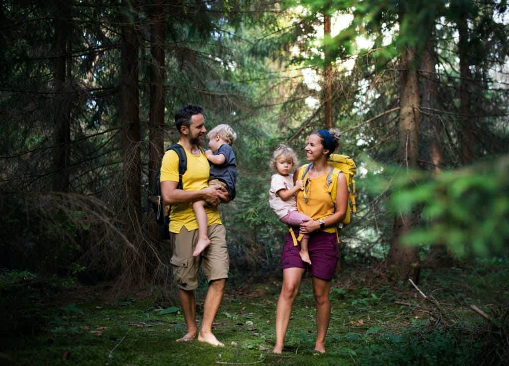 Family with small children walking barefoot outdoors in summer nature