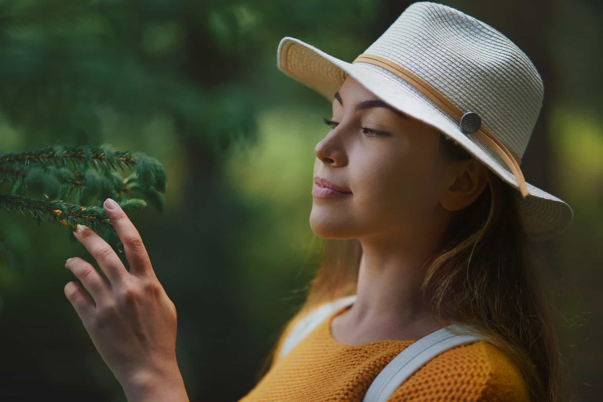Young woman on a walk outdoors in forest in summer nature, daydreaming
